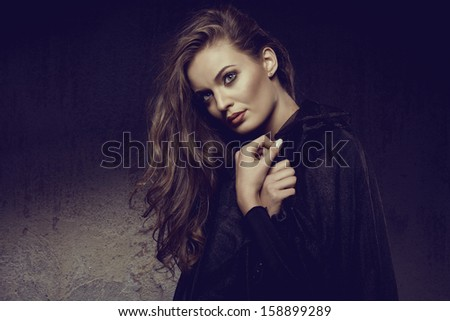 fashion photo of gothic girl in Halloween dress against the wall