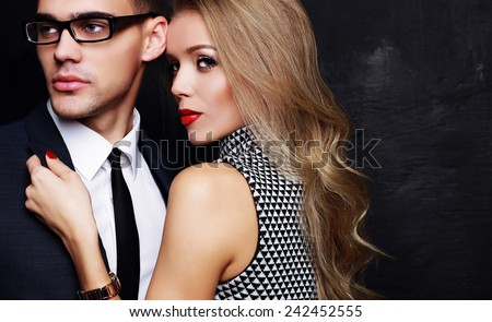 Fashion photo of office romance of sexy lovers,pretty blond woman with watch,red lipstick,and handsome brunette businessman wearing in suit,tie,glasses,they are hugging and kissing on Valentine's day - stock photo