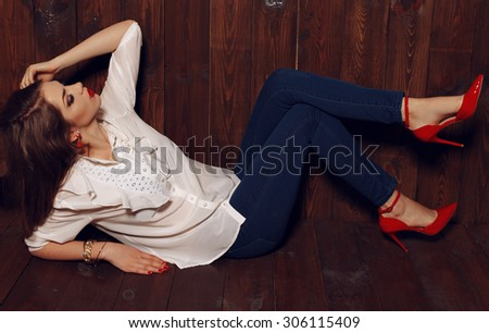 Fashion photo of pretty female in white skirt, jeans and red shoes with long blond curly hair sitting and posing on the wood background at studio - stock photo