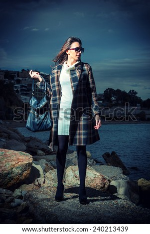 fashion photo of sensual beautiful woman with dark hair by the sea at sunset