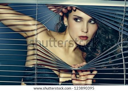 Fashion photo of sensual brunette woman with shiny curly hair - stock photo