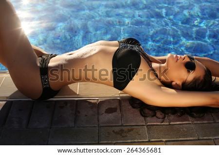 fashion photo of sexy beautiful girl with dark hair in black  bikini and sunglasses relaxing beside a swimming pool     - stock photo