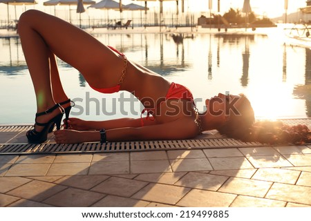 fashion photo of sexy beautiful girl with perfect body doing yoga pose beside a swimming pool - stock photo