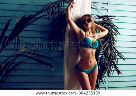 Fashion photo of sexy beautiful woman with blond curls and slim sexy body wearing a sweemsuit and posing with board for surfing on a sandy beach near bungalow - stock photo