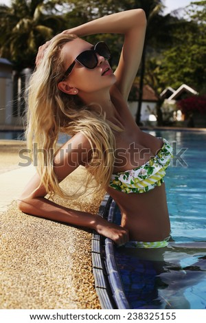 fashion photo of sexy beautiful woman with blond hair wearing colorful bikini and sunglasses relaxing in outdoor swimming pool in Thailand - stock photo