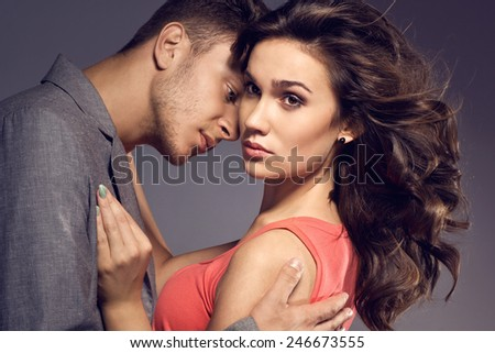 Fashion photo of sexy elegant couple in the tender passion. Studio portrait