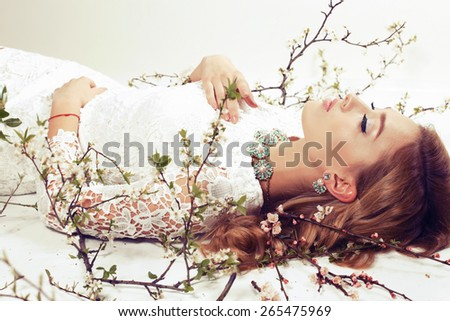 Fashion photo of sexy girl with curly hair wearing a lace dress,beautiful earrings and necklace,lying on a white background and posing around flowering trees - stock photo