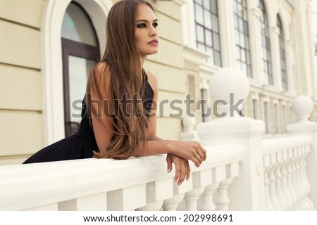 fashion photo of sexy glamour model with long dark hair in elegant black dress posing on balcony  - stock photo