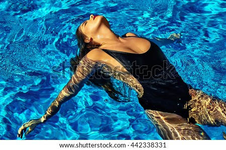 fashion photo of sexy hot beautiful girl model with dark hair in black swimwear swimming on back in swimming pool with red lips - stock photo
