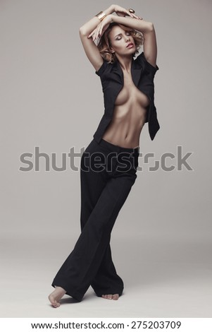 Fashion photo of sexy woman in black suit over grey studio background - stock photo
