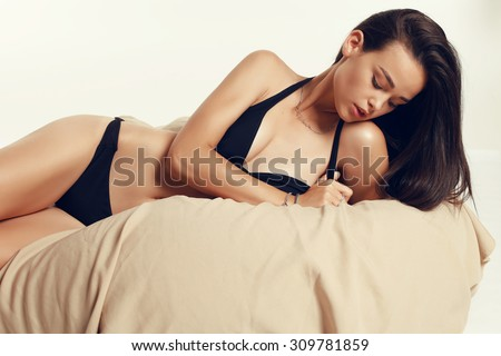 Fashion photo of sexy young brunet woman with beautiful face,straight long hair, perfect skin wearing black lingerie and posing on the ottoman at studio