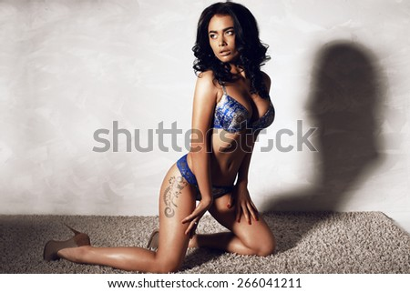 Fashion photo of sultry beautiful woman with brunette curls, tanned glowing skin and slim sexy body wearing blue lingerie,heeled shoes, sitting on a carpet and posing on a white background at studio  - stock photo