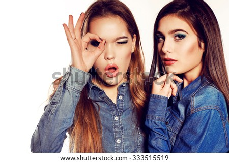 fashion photo of two beautiful young women with long dark hair and bright makeup wears casual clothes,posing in studio   - stock photo
