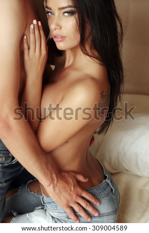 Fashion photo of two sexy beautiful lovers relax at the hotel on a bed,they are hugging and kissing - stock photo