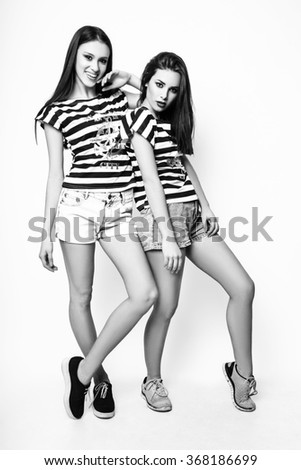 Fashion photo of two young magnificent womans on white background. Girl posing. Studio photo. Black and White image - stock photo