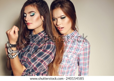 Fashion photo of two young sexy girl with long hair and bright make-up wearing in plaid shirts and watches,smiling and posing at studio