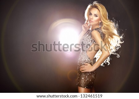 Fashion photo of young beautiful dancing woman with long flowing hair and shining dress. - stock photo
