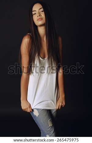 Fashion photo of young beautiful woman with brunette long hair, tanned  skin and slim sexy body wearing blue jeans and white top posing at studio - stock photo