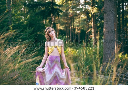 Fashion photo of young bohemian woman holding dress in a forest in evening