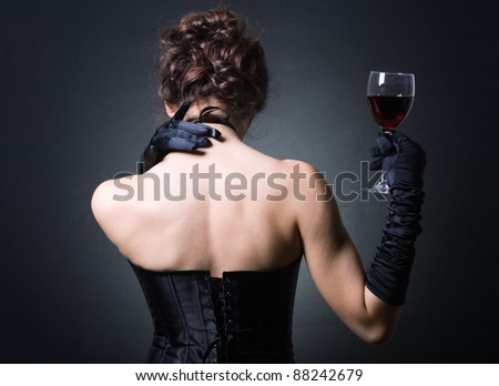 Fashion photo of young ladies in elegant evening dress with a glass of red wine. - stock photo