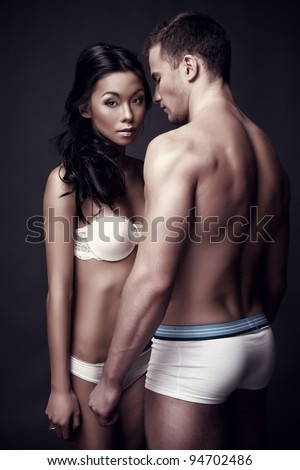 fashion photo of young lovely couple posing in lingerie on dark background