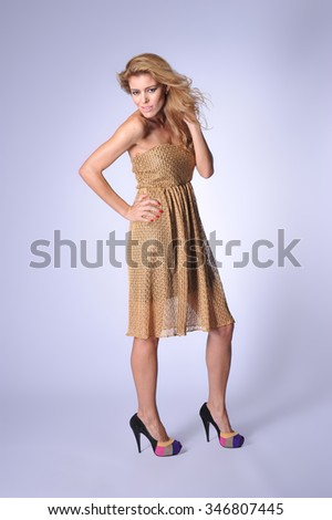 Fashion photo of young magnificent woman in golden colour dress. Women has curly wind hairs.