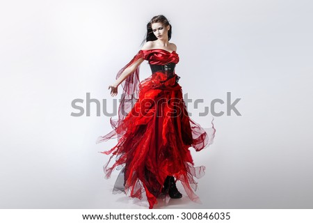 Fashion photo of young magnificent woman in red dress. Studio portrait - stock photo