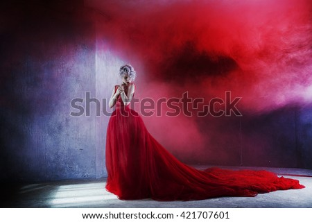 Fashion photo of young magnificent woman in red dress. Textured background, red smoke - stock photo