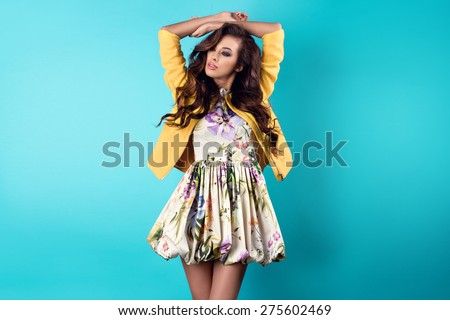Fashion photo of young magnificent woman in spring dress with flower pattern. Posing in studio - stock photo