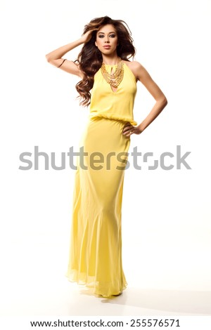 Fashion photo of young magnificent woman in yellow long dress. Girl posing. Studio photo - stock photo