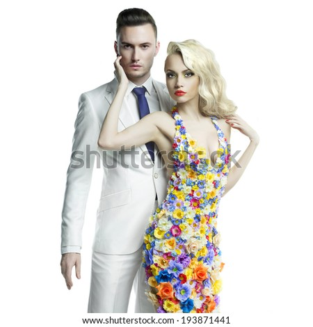 Fashion photo of young man and beautiful lady in flower dress - stock photo