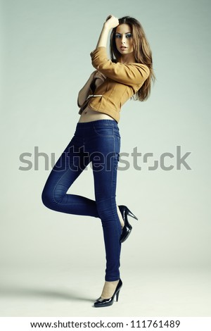 Fashion photo of young sensual woman in jeans. Studio photo - stock photo