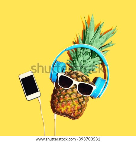 Fashion pineapple with sunglasses and headphones listens to music on smartphone over yellow background - stock photo