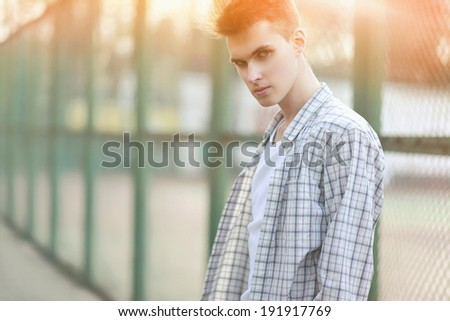 Fashion portrait handsome man in summer sunny day, strong look on camera, street fashion, hip-hop - stock photo