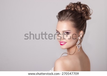 fashion portrait of a beautiful attractive girl with a gentle elegant evening wedding hairstyles high and bright make-up , with flowers in their hair and large earrings - stock photo
