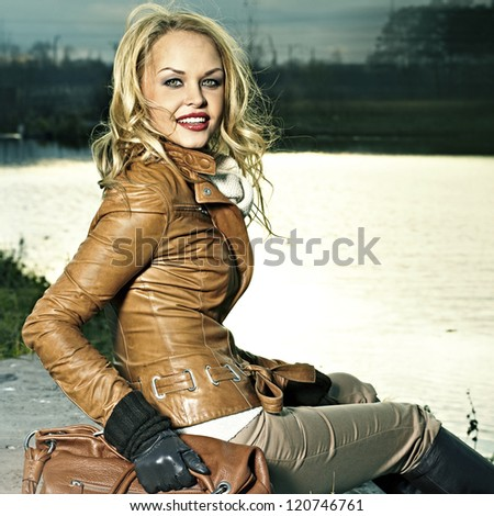 Fashion portrait of a beautiful blonde girl in a park outdoors - stock photo