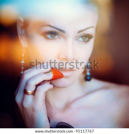 Fashion portrait of a beautiful woman with strawberry in hand - stock photo
