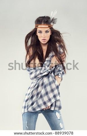 Fashion portrait of a beautiful young brunette dressed in hippie style. She is wearing a plaid shirt, skinny jeans and bandu. Wind is blowing through her hair. Taken in studio, gray background. - stock photo
