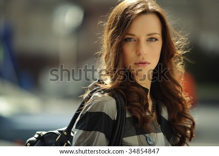 fashion portrait of a beautiful young busibesswoman in the city environment - stock photo
