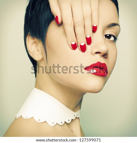 Fashion portrait of a beautiful young lady with bright nail polish - stock photo