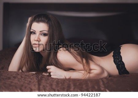 Fashion portrait of a beautiful young sexy woman on the bed - stock photo