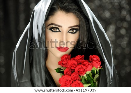 Fashion Portrait of a beautiful young woman holding a bouquet of red roses with a black cloak and veil - stock photo