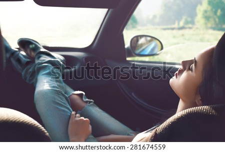Fashion portrait of a beauty brunette girl in blue jeans sitting in the car. Summer days. Relax. - stock photo