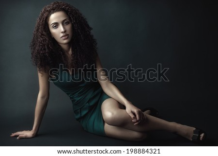 Fashion portrait of a beauty brunette girl with curly hair in green dress.