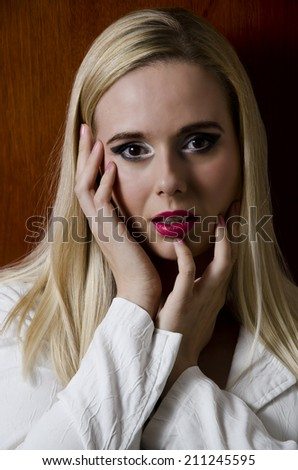 fashion portrait of a blonde woman against a wooden textured background