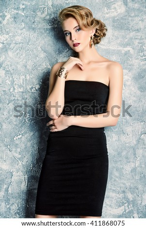 Fashion portrait of a charming young woman in black dress with evening make-up and hairstyle. Beauty, fashion. - stock photo