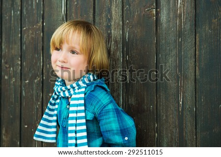 Fashion portrait of a cute little blond  boy against wooden background, wearing emerald shirt and scarf - stock photo
