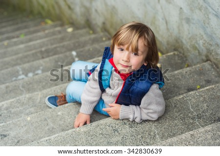 Fashion portrait of a cute little blond boy sitting on stairs in a city, wearing beige pullover and blue jacket