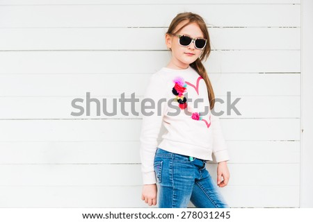 Fashion portrait of a cute little girl against white background, wearing sweatshirt and jeans - stock photo