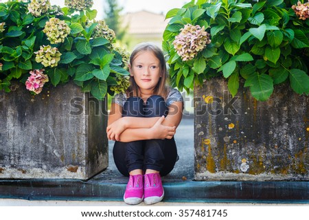Fashion portrait of a cute little girl of 7-8 years old, wearing bright pink shoes - stock photo